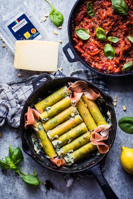 """Cannelloni met gerookte ricotta, spinazie en venkel. Prep Time 10 mins Cook Time 2 hrs 20 mins Total Time 2 hrs 30 mins Als het zomer wordt krijg ik telkens weer die onweerstaanbare drang… Italië roept! Je hoort het misschien niet, maar ik wel! Italiaanse gerechten zijn vaak zo snel klaar dat niemand de moeite doet om de BBQ aan te steken. Doe het misschien toch maar eens! Zo kan je een smoky touch geven aan je favoriete recepten zoals bij deze """"smoky ricotta stuffed cannelloni"""". Laat het je smaken! Course: Hoofdgerecht Cuisine: Italiaans Keyword: BBQ sauce, cannelloni, gerookte, italiaans, pelletgrill, ricotta, spinazie, Traeger, vulling Servings: 4 personen Ingredients Tomatensaus 1 rode ui 3 teentjes look 2 takken verse rozemarijn 3 takjes verse oregano 1 laurierblaadje 3 takjes verse tijm 1 goede scheut rode vermouth 6 San Marzano tomaten verse basilicum naar smaak peper en zout naar smaak Smoky Ricotta vulling 250 gr. ricotta 200 gr. verse spinazie 1 venkel peper en zout naar smaak citroensap naar smaak 6 sneden Prosciutto 1 snuifje nootmuskaat Afwerking 1 handvol pijnpboompitten gemalen mozzarella kaas naar smaak Vers gemalen Montasia Fresco kaas naar smaak 12 cannelloni tubes Instructions Bereid je BBQ voor op een indirecte sessie op lage temperatuur. 75°C op de Traeger zorgt voor een mooie rookgeneratie. Rook hierop de ricotta (in een pannetje), spinazie (in een zeefje) en de venkel voor anderhalf tot twee uur. Heb je geen pelletgrill dan kan deze stap ook gebeuren door koud te roken met een cold smoke generator. Als het goed gegaan is kleurt je ricotta na deze fase lichtgeel. Tomatensaus maken Terwijl de vulling rookt kan je de saus voorbereiden. Deze hoeft niet extra gerookt te zijn aangezien de vulling al een subtiele rooksmaak zal meekrijgen. Zet een gietijzeren pannetje op een medium hittebron en voeg hieraan olie toe. Bak de verse kruiden (behalve de basilicum) kort aan in de olie zodat de smaken mooi loskomen. Snipper ondertussen de rode ui en voeg de"""